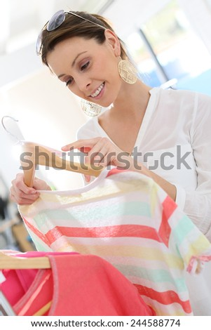 Beautiful woman in clothing store looking at price tag - stock photo