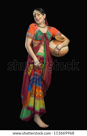 Beautiful woman in colorful lehenga choli carrying water pot - stock photo