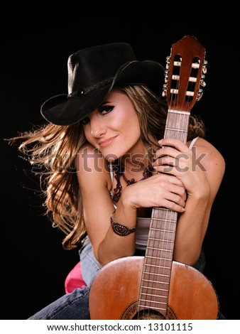Beautiful Woman in Country Western Fashion Holing A Guitar - stock photo