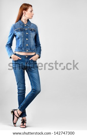 Beautiful woman in denim clothes on grey background. Space for text. - stock photo