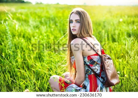 Beautiful woman in dress and bag sitting on the glade  - stock photo
