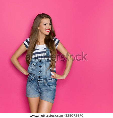 Beautiful Woman In Dungarees Looking At Copy. Three quarter length studio shot on pink background. - stock photo