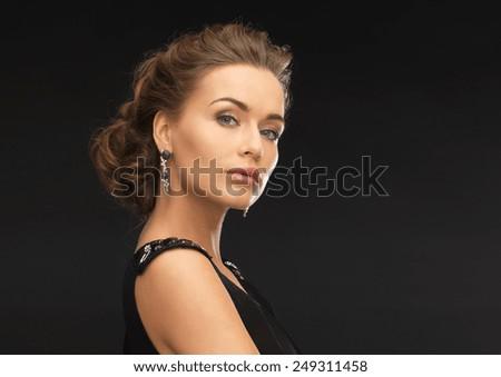 beautiful woman in evening dress wearing diamond earrings - stock photo
