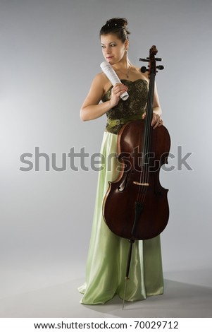 Beautiful woman in evening dress with cello and notes - stock photo