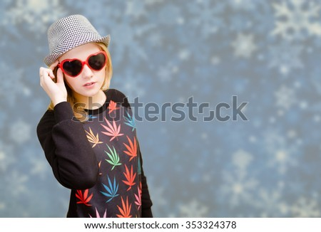 Beautiful woman in fancy sunglasses smiling on snowflakes blurred background