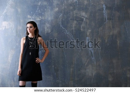 Beautiful woman in fashion clothes on grunge wall background