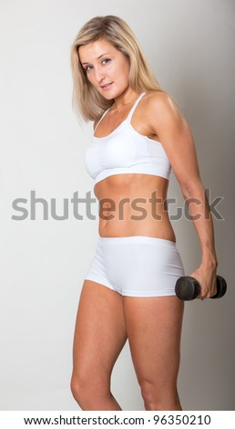Beautiful woman in fitness outfit using weights - stock photo