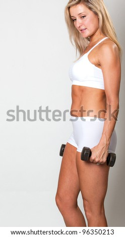 Beautiful woman in fitness outfit using weights