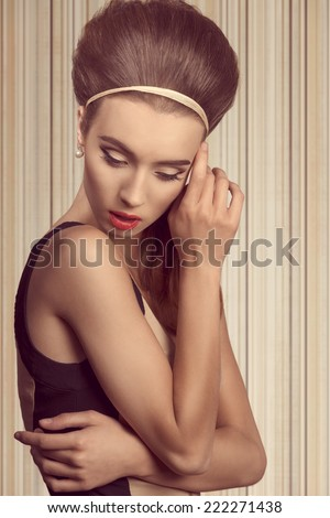 beautiful woman in fitted cream and black dress is looking down. She has got big blue eyes, brown big hairstyle and she is wearing hairband and pearls on her ea - stock photo