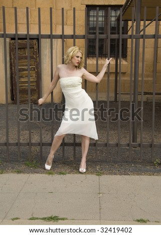 Beautiful woman in front of a metal fence