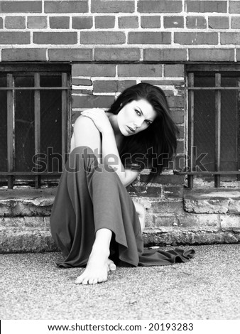 Beautiful woman in front of an old brick wall