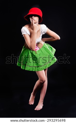 Beautiful woman in german beer girl costume showing keep a quiet gesture over black background - stock photo