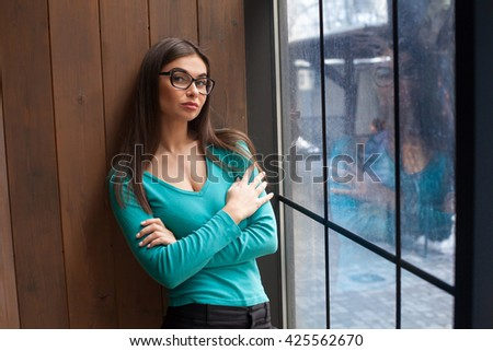 Beautiful woman in glasses is standing near the window