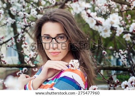 Beautiful woman in glasses on a background of a blossoming tree. - stock photo