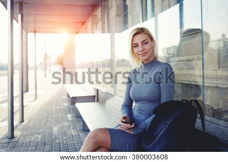 Beautiful woman in good mood looking at camera while waiting for a call on her cell telephone, pretty female using smart phone while sitting on a bus stop against sun rays background with copy space - stock photo