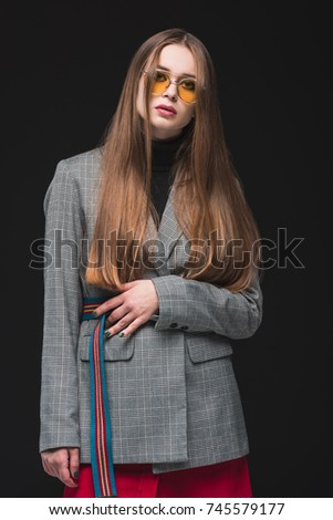 Beautiful woman in gray jacket and yellow sunglasses standing isolated on black