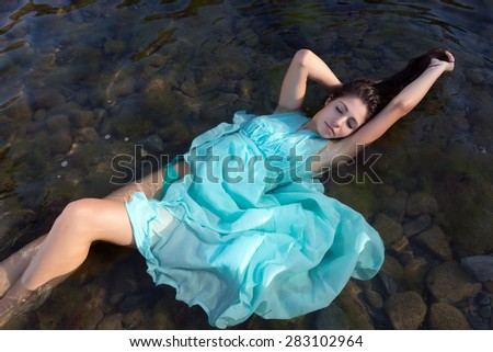 Beautiful woman in green dress floating in the shallow beach waters - stock photo
