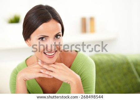 Beautiful woman in green shirt contemplating while looking at the camera - copy space - stock photo