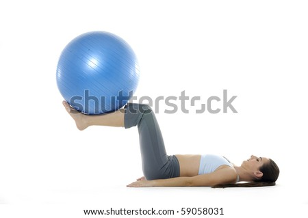 beautiful woman in gym outfit exercising with a pilates ball - stock photo