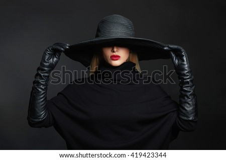 Beautiful woman in hat and leather gloves. Retro fashion model girl.black hat with large brim.halloween witch - stock photo