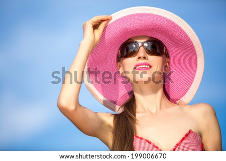 Beautiful woman in hat and sunglasses. Fashion woman in hat over blue sky background - stock photo