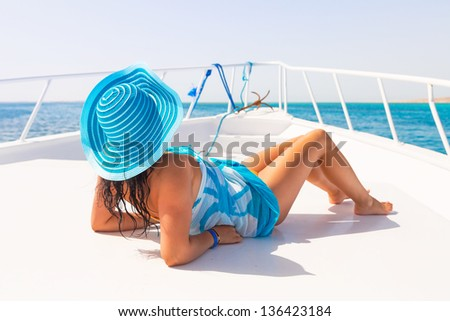 Beautiful woman in hat relaxing on the yacht cruise - stock photo