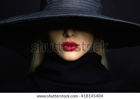 Beautiful woman in hat. Retro fashion.summer hat with large brim over dark background - stock photo