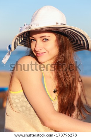 Beautiful woman in hat with long hair on the beach. Closeup portrait