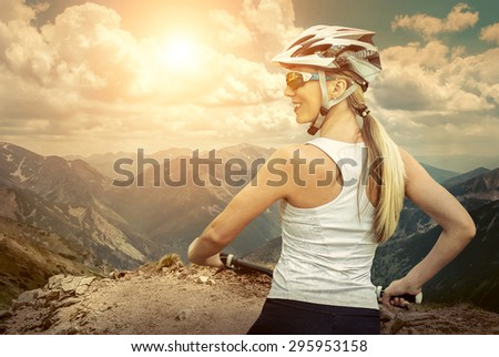 Beautiful woman in helmet and glasses stay on the bicycle around mountains. - stock photo