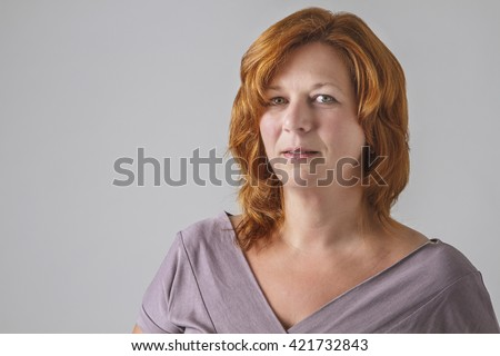 beautiful woman in her forties with red hair, wearing a grey shirt
