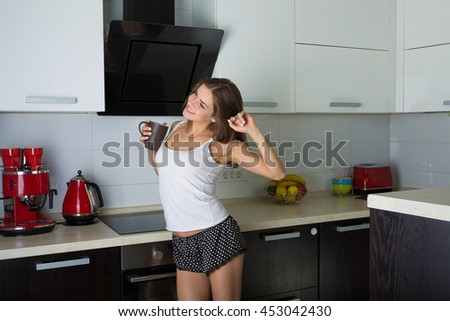 Beautiful woman in her kitchen in the morning preparing breakfast