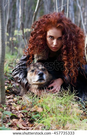 Beautiful woman in jacket poses with dog in sunny autumn forest