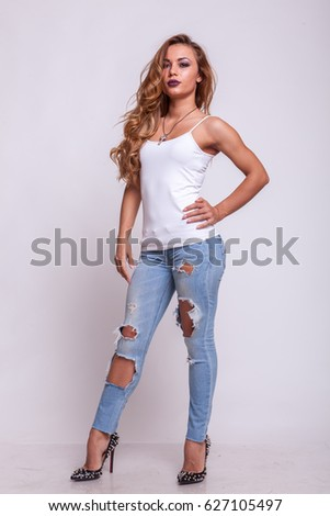 Beautiful woman in jeans and white shirt on studio background