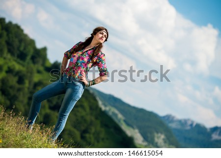 beautiful woman in jeans standing on the grass - stock photo