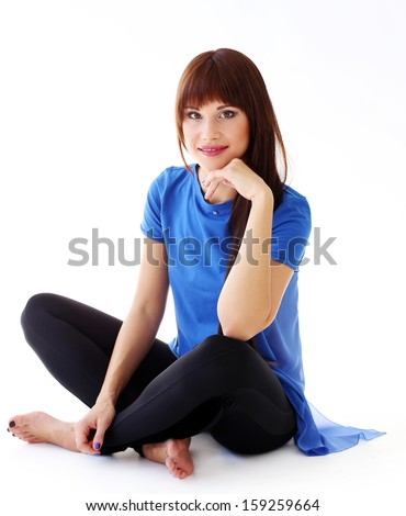 Beautiful woman in leggings and a blue shirt is sitting on the floor and posing - stock photo