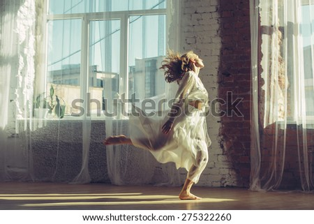 Beautiful woman in light interior with big windows listening music and dancing. Home comfort concept