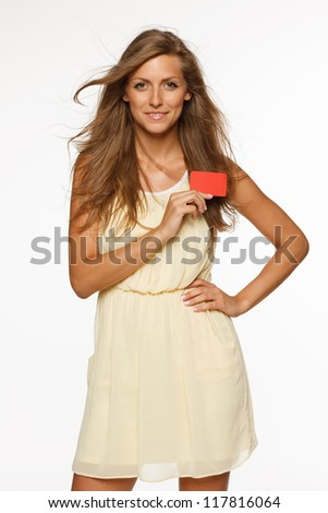 Beautiful woman in light summer dress holding empty credit card isolated on white background - stock photo