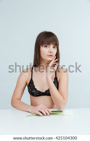 Beautiful woman in lingerie sitting at the table with tulip isolated on a white background and looking at camera - stock photo