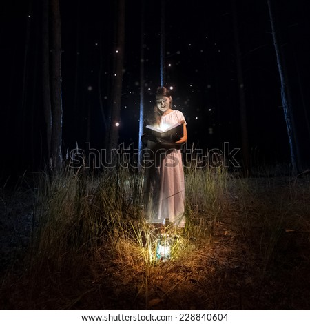 Beautiful woman in long dress reading big old book at mysterious forest with fireflies - stock photo
