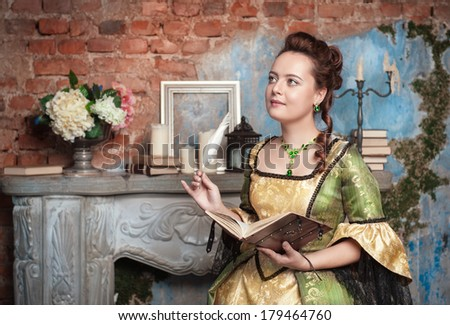 Beautiful woman in long medieval dress writing in diary  - stock photo