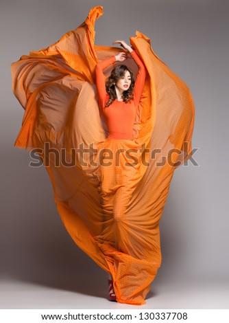beautiful woman in long orange dress posing dynamic in the studio - stock photo
