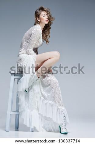beautiful woman in long white dress posing fashion in the studio - stock photo