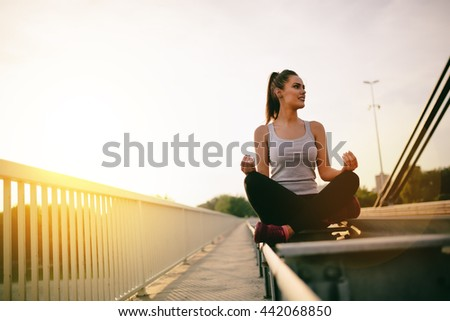 Beautiful woman in lotus position on bridge next to cars - concept - stock photo