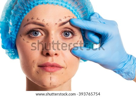 Beautiful woman in medical headwear with sketches on face, surgeon in medical gloves is examining her face, isolated on a white background - stock photo
