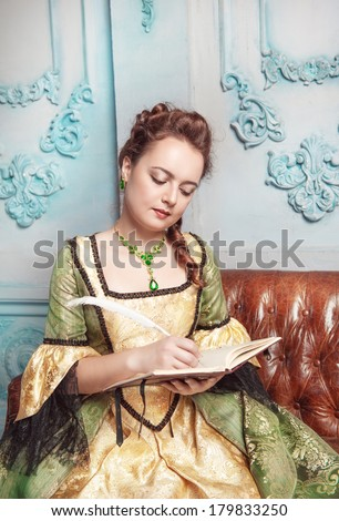 Beautiful woman in medieval dress writing in diary - stock photo