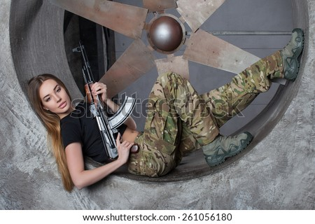 Beautiful woman in military trousers and boots lying on back with arms in cookies.Beautiful young woman in camouflage clothing, guns in her hands, she looks into the camera lying on the back - stock photo