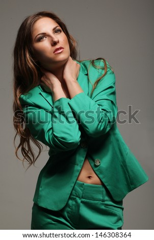 Beautiful woman in modern bright suit over greu