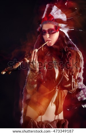 Beautiful woman in native american costume posing with peace-pipe in a studio with double exposure on the picture