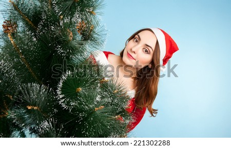 Beautiful woman in new year costume with fir-tree on blue background - stock photo