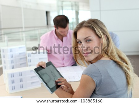 Beautiful woman in office using electronic tablet - stock photo